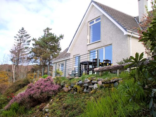 This view of the terrace at Gairloch View Guest House shows the large picture windows of the guest dining room from which there are panoramic sea views across Loch Gairloch towards the Isle of Skye.